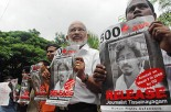 Activists hold up posters of Tissanayagam on Aug. 31